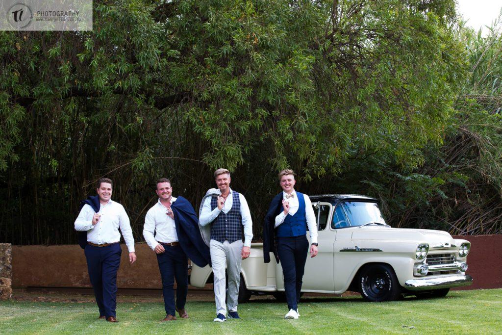 Groom & Groomsmen walking away from vintage car