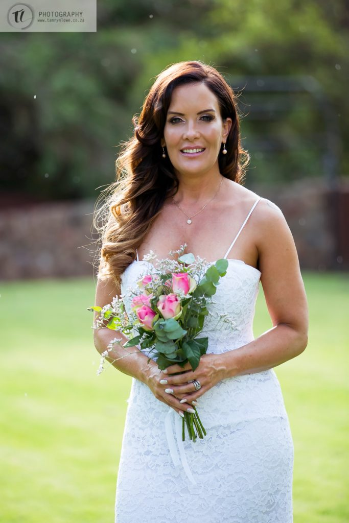 Bride with bouquet and rain in the background