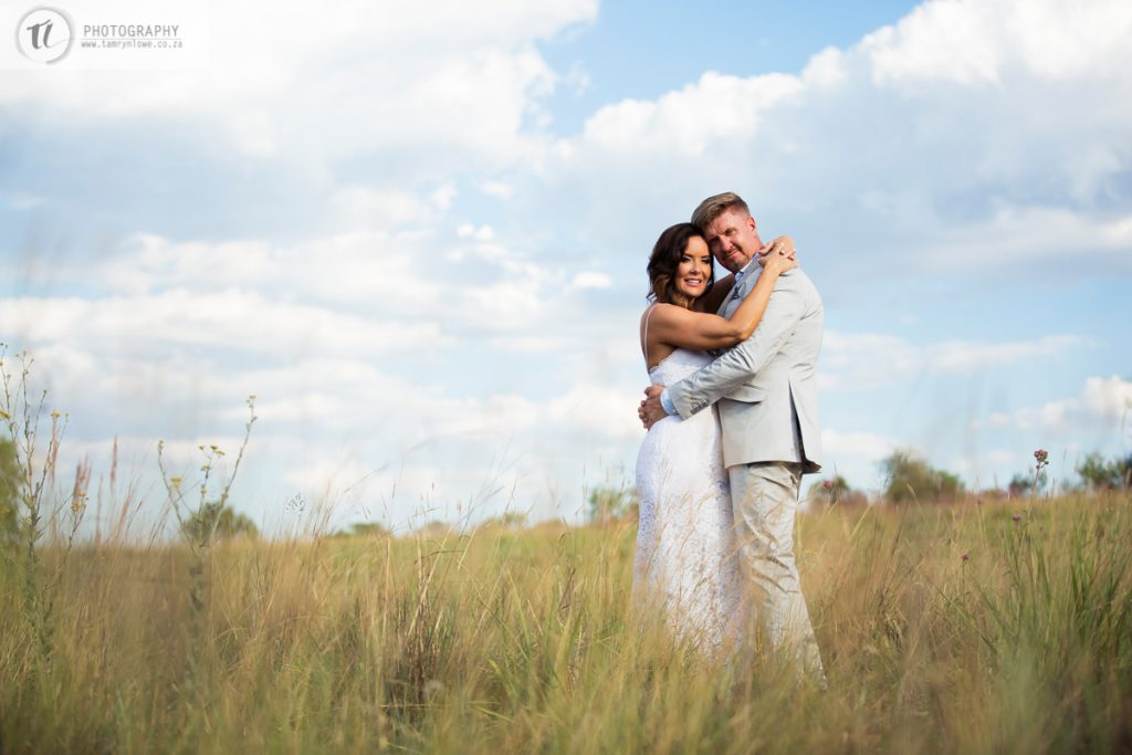 Bride & Groom pose for picture in long dry grass