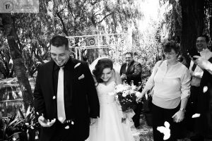 Bride and groom walking out after wedding with confetti being thrown