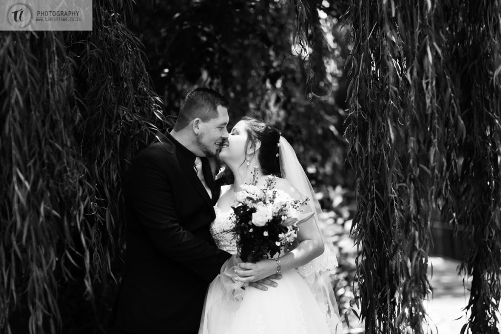 Bride & Groom kissing under a tree