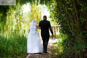 Bride & Groom walking away through trees
