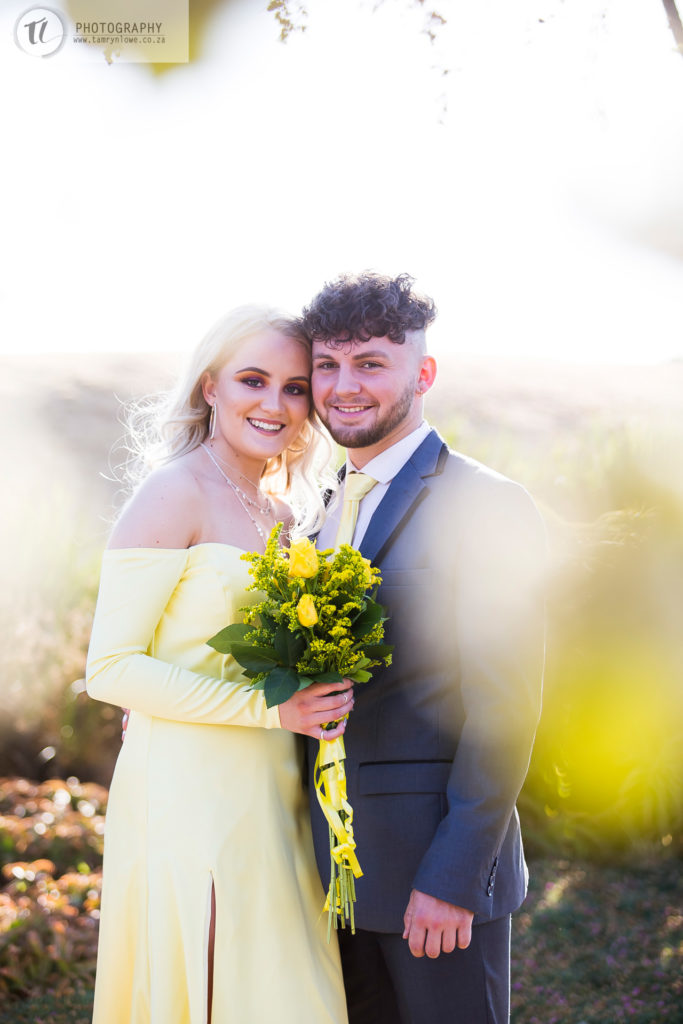 young couple posing together holding flowers