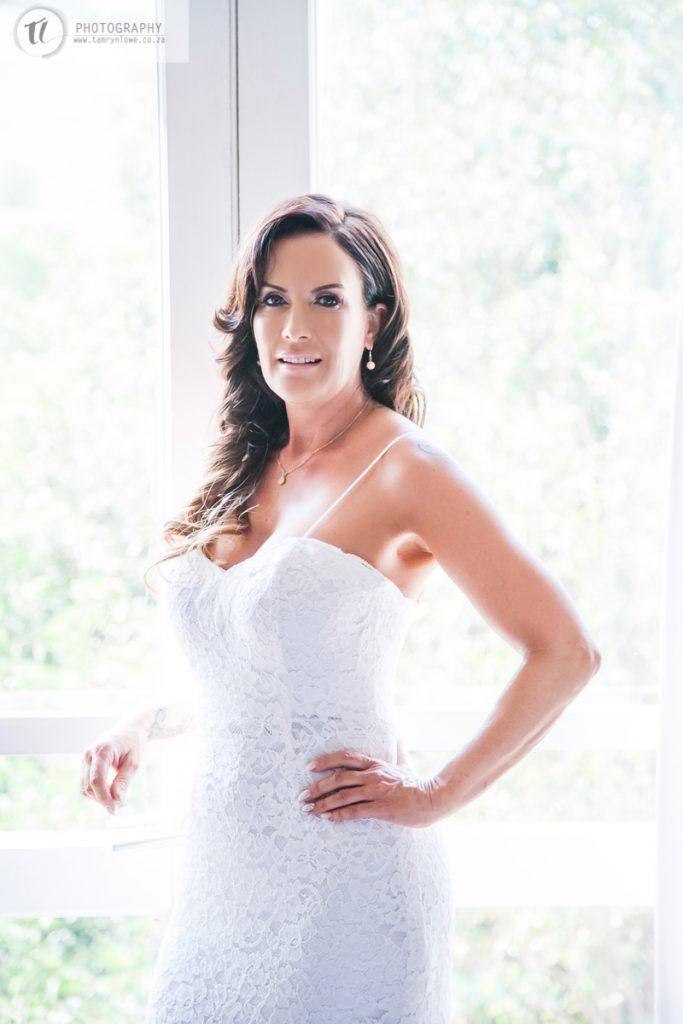 Bride posing in front of window