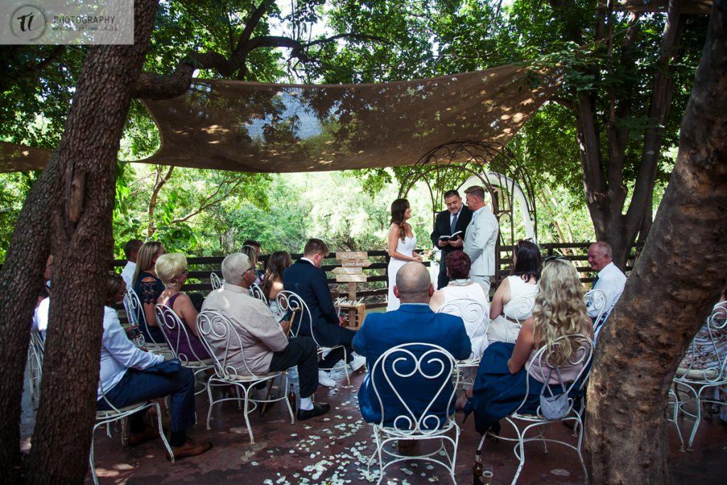Bride & Groom saying vows under trees